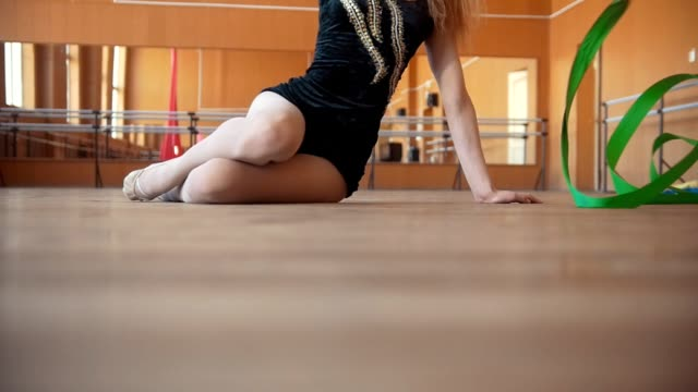 vidéos et rushes de femme assise sur le sol en effectuant l'exercice avec un ruban - abaisser