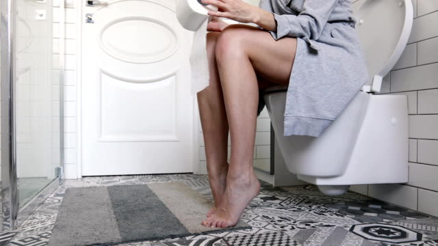 Woman sitting on the toilet holding toilet paper Woman sitting on the toilet holding toilet paper in her hands bathroom stock videos & royalty-free footage
