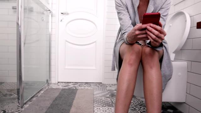 stockvideo's en b-roll-footage met vrouw zittend op het toilet met telefoon - cell phone toilet