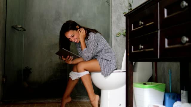 stockvideo's en b-roll-footage met vrouw zitten op toilet gebruik tablet computer jong meisje touch scherm online chatten - cell phone toilet