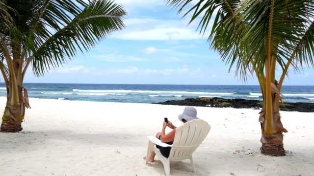 Woman sitting on tropical beach under palm trees on deckchair typing SMS on mobile phone device video