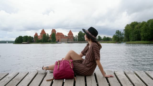 woman sitting on wooden pier near trakai castle - lituania video stock e b–roll