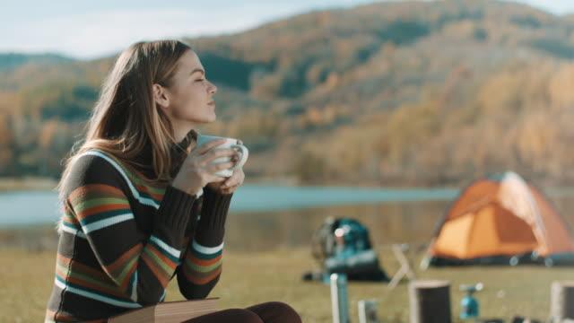 座って、本を読んで、湖のそばのキャンプ旅行にコーヒーを飲む女性 ビデオ