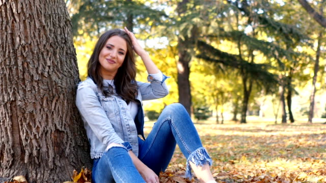 woman sitting under a tree - woman portrait forest video stock e b–roll
