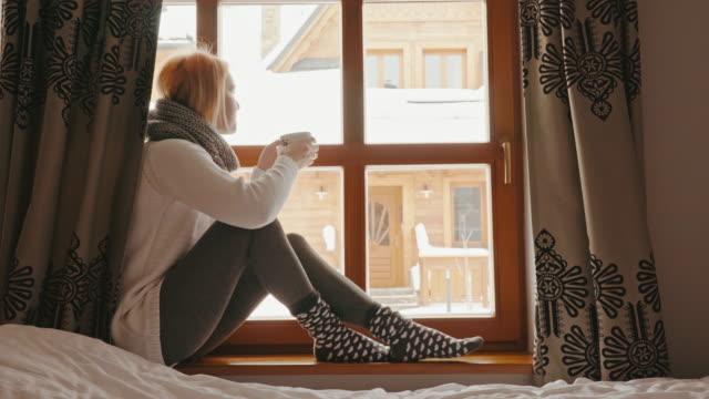 frau sitzt mit einer tasse tee in einem winter-fenster - cozy stock-videos und b-roll-filmmaterial