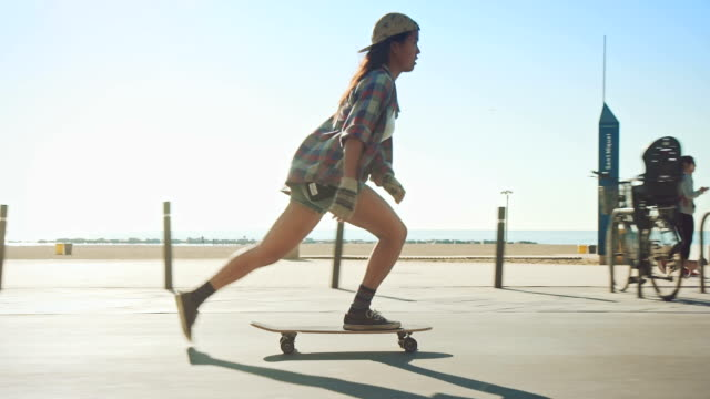 Woman skateboarding at beach A young woman skating with her skateboard at a beach promenade. Its a sunny summer day. skateboarding stock videos & royalty-free footage