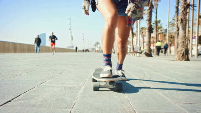 woman skateboarding at beach - sprzęt sportowy filmów i materiałów b-roll