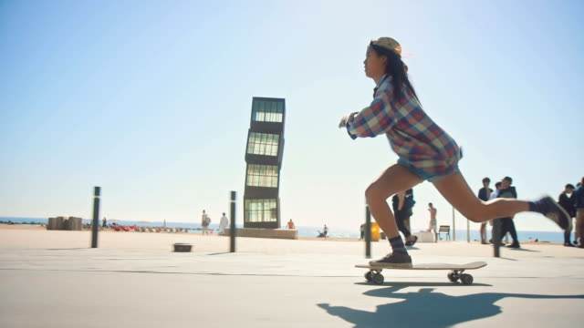 woman skateboarding at beach - skateboarding stock videos and b-roll footage
