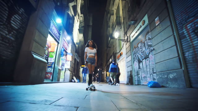 Woman skateboarding on street at night video