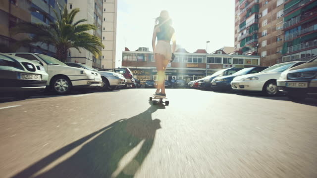 woman skateboarding on street - skateboarding stock videos and b-roll footage