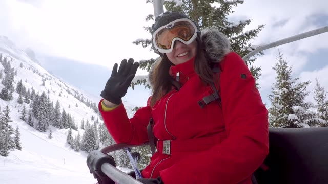 Woman Skier Climbs On The Chair Lift To The Top Of The Mountain And Waving Hand