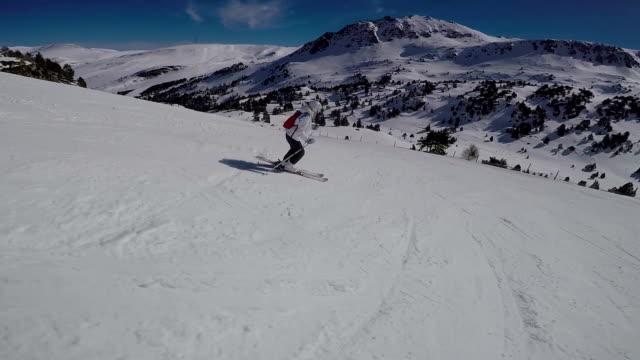 A woman skiing on a ski track, the sun and snowy mountains. video