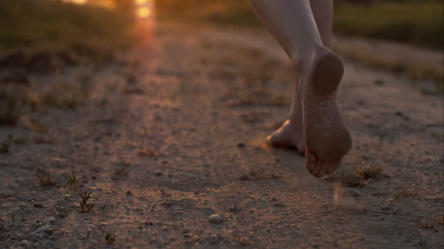 Woman skipping barefoot on a dirt road video