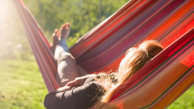 woman sleeping in a swinging hammock in backyard at sunrise - amaca video stock e b–roll