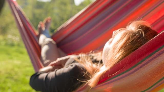 일출에 뒤뜰에서 스윙 해먹에서 자 고 하는 여자 - 환희 스톡 비디오 및 b-롤 화면