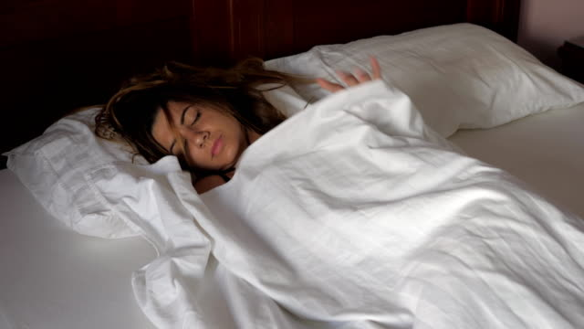 vídeos de stock e filmes b-roll de woman sleeping in bed with her and begin to constrict blanket she does not give - puxar