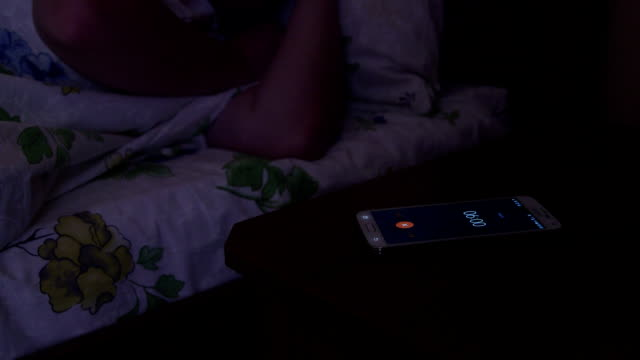 Woman sleeping on bed with alarm clock on digital cell phone display video