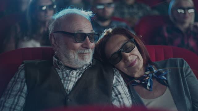 woman sleeping on man's shoulder at cinema - para aranżacja filmów i materiałów b-roll