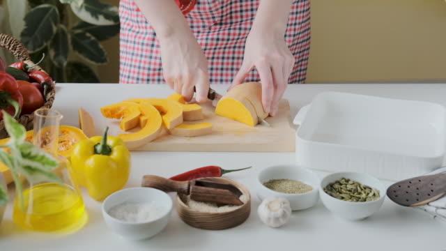 woman slicing a pumpkin. hands of a woman slicing a pumpkin in the kitchen. - pumpkin стоковые видео и кадры b-roll