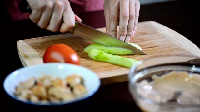 vídeos de stock, filmes e b-roll de mulher, corte o pepino. mãos femininas cortar anéis de pepino verde. - comida salgada