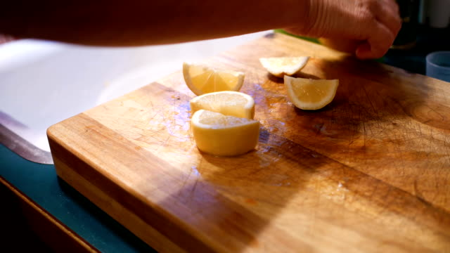 Woman slicing lemons on a cutting board in kitchen with knife Woman slicing lemons on a cutting board in kitchen with knife cooking utensil stock videos & royalty-free footage