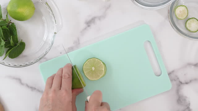 Woman slicing lime on cutting board, close up video, marble background, view from above