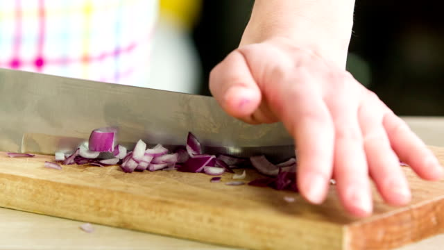 Woman Slicing Red Onion On Wooden Board video