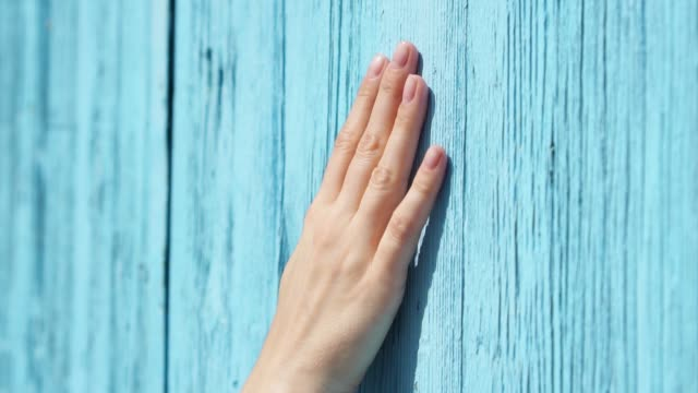 Woman slide hand against blue-colored wooden door in slow motion. Female hand touch surface of wood