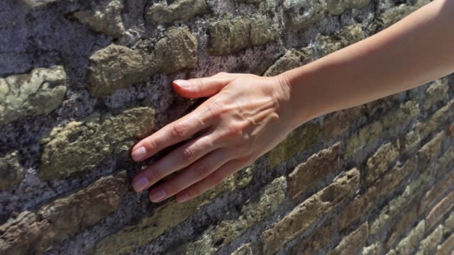 Woman slide hand against old red brick wall in slow motion. Female hand touch rough surface of stone