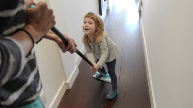 woman sliding child with dust mop funny scene of three years old laughing child sliding on flat dust mop while woman sweeping the floor in corridor at home cleaning stock videos & royalty-free footage