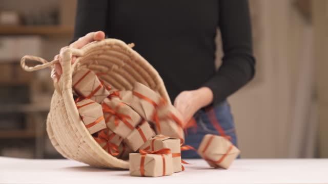 vidéos et rushes de femme fracassant de petites boîtes de cadeau rectangulaires enveloppées dans le papier brun et décorées avec des rubans rouges hors du panier d'osier. isolé, sur fond brouillé - emballé