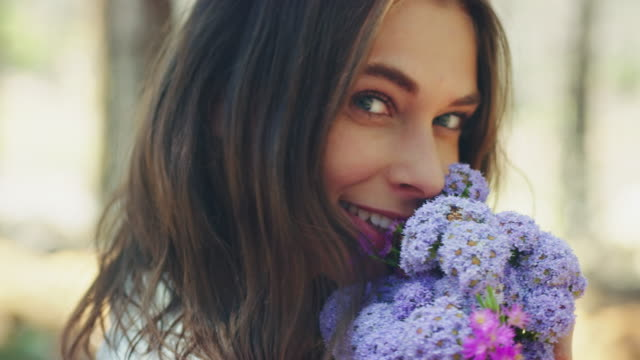 Woman smelling at flowers A young woman standing in the forest. She is holding a flower bouquet and smells on it. Trees can be seen in the background. smelling stock videos & royalty-free footage