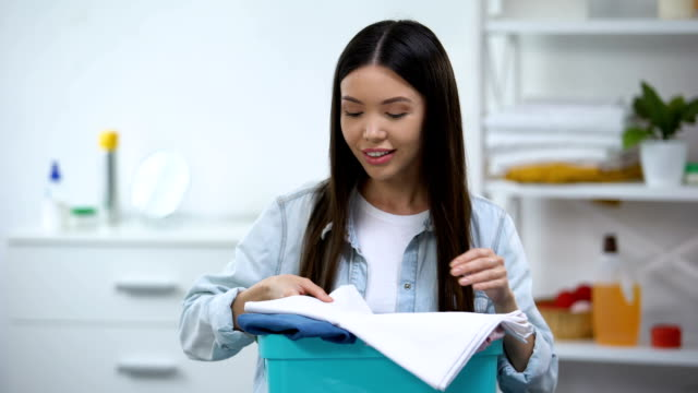 Woman smelling clean fresh linens and smiling at camera, fabric softener
