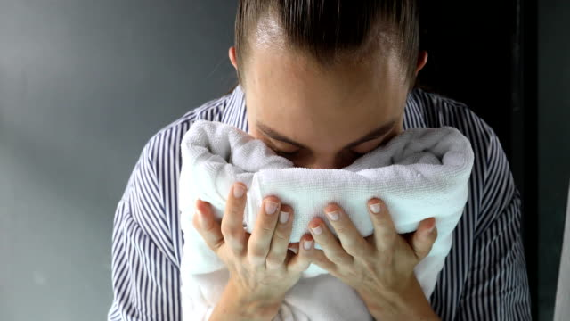 Woman smelling clean towel