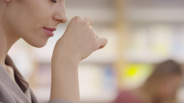 Woman Smelling Cream on her Hand Tilt up shot with close up of attractive young woman smiling and smelling her hand after putting on cream at cosmetic store smelling stock videos & royalty-free footage