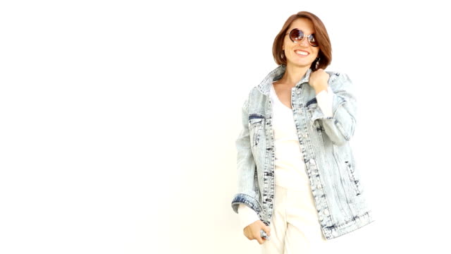 Woman smiling and posing on white background wearing sunglasses and denim jacket