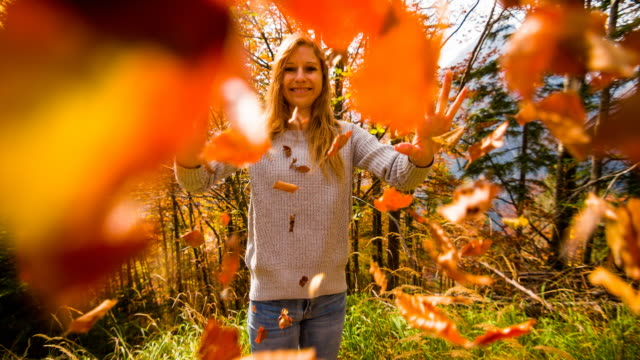 Woman smiling and throwing colorful leaves towards the camera