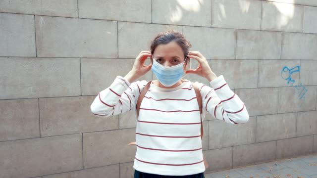 kvinna leende bakom skyddsmask utomhus - face mask bildbanksvideor och videomaterial från bakom kulisserna
