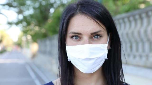 koruyucu maskenin arkasında gülümseyen kadın - orta yetişkin stok videoları ve detay görüntü çekimi