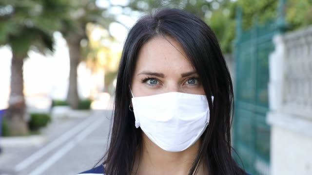 Woman smiling behind the protective mask - video