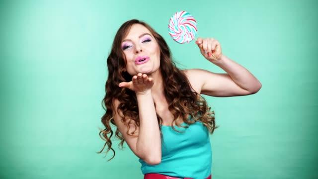 婦女微笑的女孩與棒棒糖糖果在綠色4k - 波板糖 個影片檔及 b 捲影像