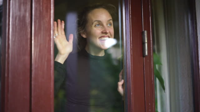 woman smiling looks out of window from inside home - sventolare la mano video stock e b–roll