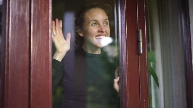 woman smiling looks out of window from inside home - machać filmów i materiałów b-roll