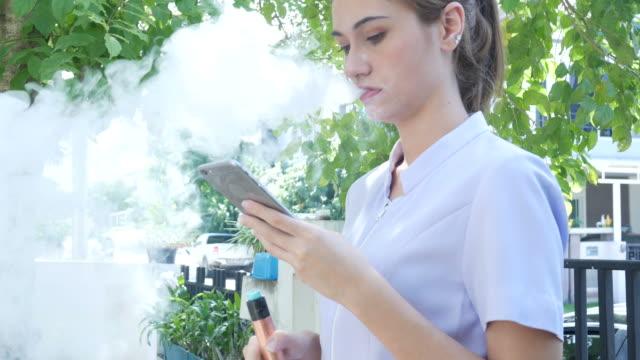 woman smoke e-cigarette and using phone video