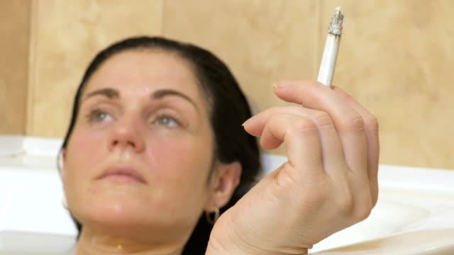 Woman smoking in Bathtub.Stock footage video - vídeo