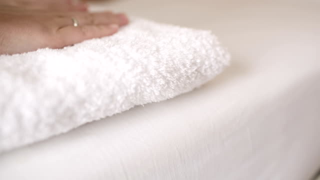 Woman smoothing a fresh white towel video