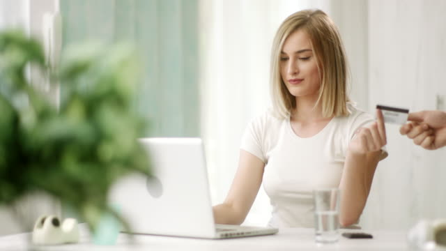 Woman snapping fingers and getting credit card for online shopping Young blonde woman snapping fingers and getting credit card for online shopping snapping stock videos & royalty-free footage