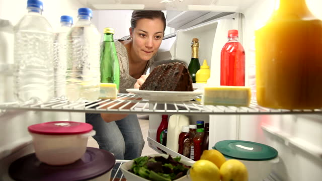 Woman sneaks bite of chocolate cake Woman opens refrigerator and sneaks bite of chocolate cake fridge stock videos & royalty-free footage