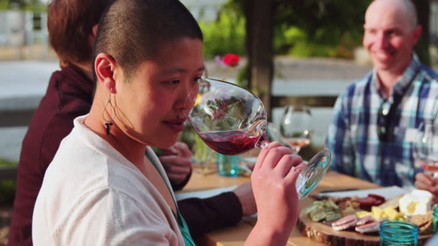 Woman Sniffing and Swirling Wine at al Fresco Wine Tasting - Slow Motion A group of men and women enjoying a day out at a winery in Sonoma County, California. They are sitting at a long table, tasting delicious wine in large glasses. winetasting stock videos & royalty-free footage