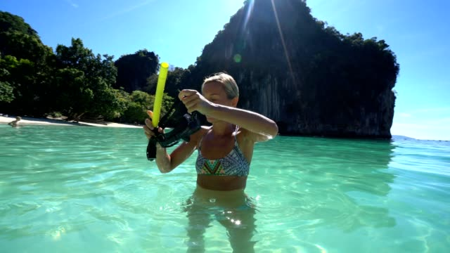 vídeos de stock e filmes b-roll de a woman snorkeling in the warm turquoise water of thailand - mergulhar